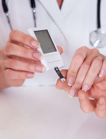 glucometer: Doctor testing a patients glucose level after pricking his finger to draw a drop of blood and then using a digital glucometer