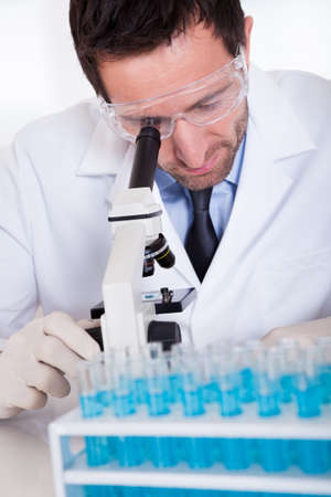 pathologist: Male pathologist or lab technician using a microscope with a rack of test tubes containing blue liquid in front of him Stock Photo