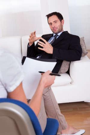 terapia psicologica: Vista por la espalda de un hombre de negocios recostado c�modamente en un sof� hablando con su psiquiatra explica algo Foto de archivo