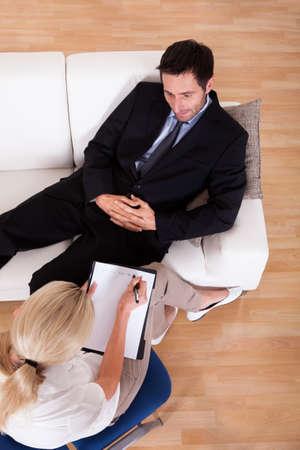 terapia psicologica: Vista superior de un hombre de negocios recostado cómodamente en un sofá hablando con su psiquiatra explica algo