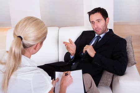 n�vrose: Dessus l'�paule d'un homme d'affaires couch� confortablement sur un canap� de parler � son psychiatre expliquer quelque chose Banque d'images
