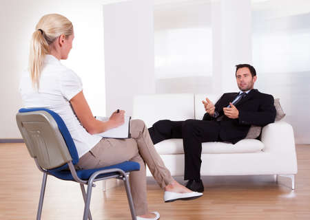 session: Over the shoulder view of a business man reclining comfortably on a couch talking to his psychiatrist explaining something