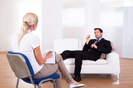 counseling: Over the shoulder view of a business man reclining comfortably on a couch talking to his psychiatrist explaining something