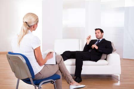 terapia psicologica: Vista por la espalda de un hombre de negocios recostado cómodamente en un sofá hablando con su psiquiatra explica algo Foto de archivo