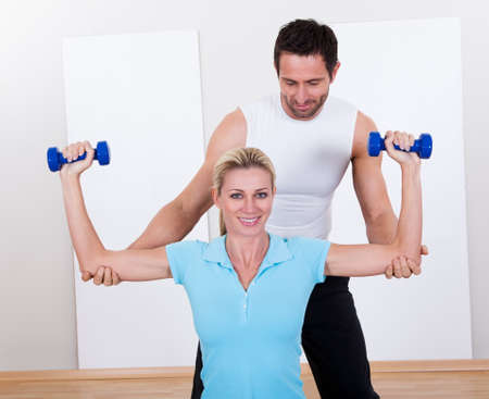 Fitness instructor helping a woman with her workout guiding her arm behind her head as she lifts dumbbells photo