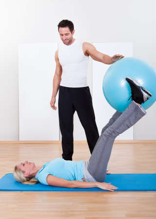 Handsome fit instructor helping a woman with pilates exercises extending and stretching her leg as she sits on a gym ball photo