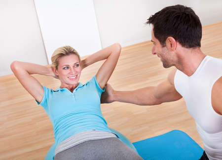 Fitness instructor teaching sit ups to a beautiful young blonde woman while working out in a gym photo