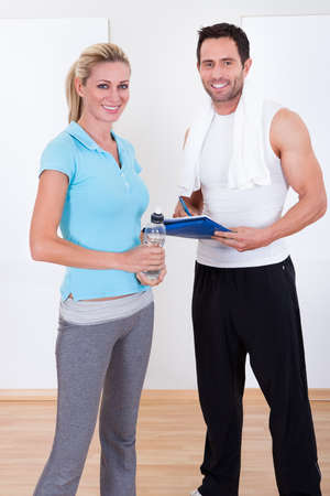Fitness instructor taking notes after a workout with an attractive athletic young woman standing alongside Stock Photo - 16874364