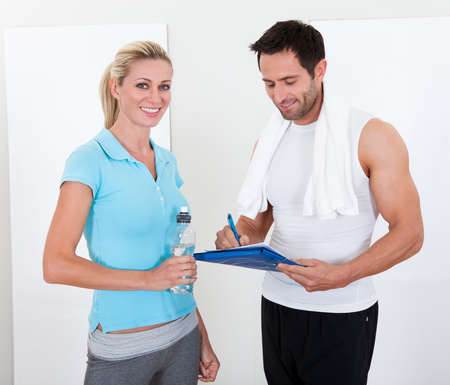 Fitness instructor taking notes after a workout with an attractive athletic young woman standing alongside photo