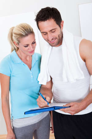 fitness trainer: Fitness instructor taking notes after a workout with an attractive athletic young woman standing alongside Stock Photo