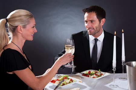 Romantic couple sitting having dinner in an elegant restaurant toasting each other with flutes of champagne Stock Photo - 16874294