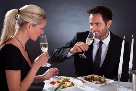 Romantikus pár ül vacsorázni egy elegáns étteremben pirítós egymást fuvolák pezsgővel Stock fotó