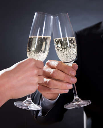 Romantic couple sitting having dinner in an elegant restaurant toasting each other with flutes of champagne photo