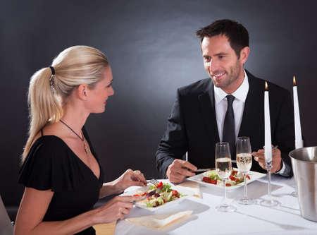 luz de velas: Pareja romántica sentado cenando en un restaurante elegante Foto de archivo