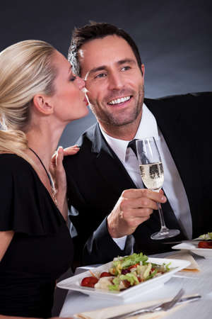 pareja comiendo: Pareja rom�ntica sentado cenando en un restaurante elegante Foto de archivo
