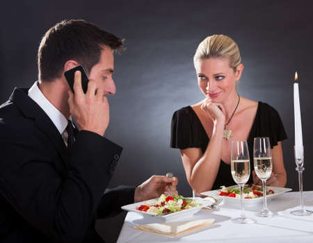 Man taking a mobile call during a romantic dinner in an elegant restaurant with the woman stretching her hand across the table as though to take it away from him photo