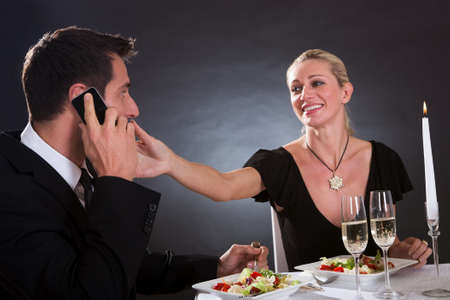 dine: Man taking a mobile call during a romantic dinner in an elegant restaurant with the woman stretching her hand across the table as though to take it away from him