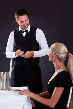 steward: Waiter taking order from woman in restaurant