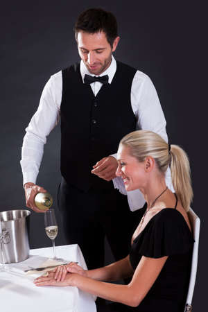 Waiter serving champagne to a beautiful blonde woman seated at a table in an elegant restaurant photo