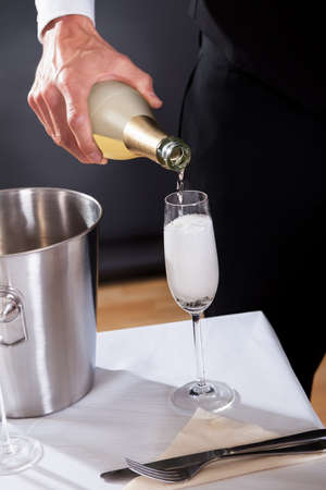 Waiter serving champagne to at the restaurant photo