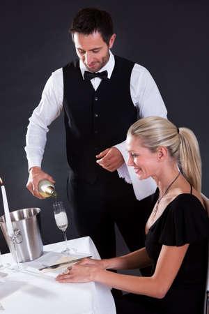sirvientes: Camarero que sirve champán a una hermosa mujer rubia sentada en una mesa en un restaurante elegante