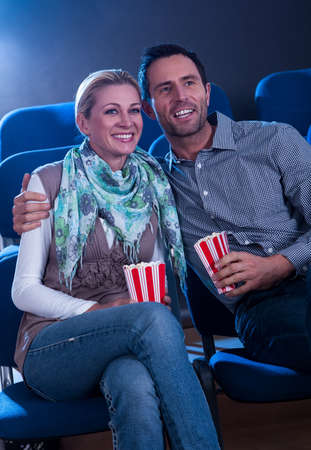 out of date: Stylish couple enjoying a movie together sitting in a cinema with their iconic striped containers of popcorn Stock Photo