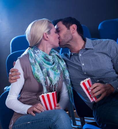 pareja besandose: Elegante pareja tiene momento romántico en un cine