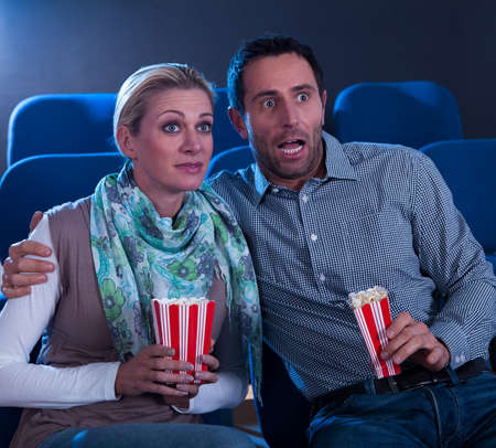 reacting: Couple sitting watching a movie in a cinema with containers of popcorn reacting in horror to something on screen