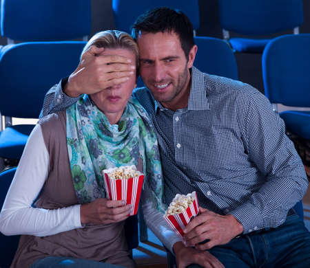Couple sitting watching a movie in a cinema with containers of popcorn reacting in horror to something on screen photo