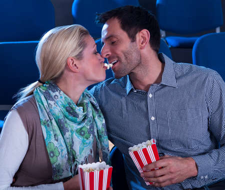 Loving couple sharing their popcorn while seated at the cinema watching movies photo