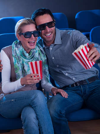 A sweet couple watching a 3d movie and enjoying with each other in movie theater. photo