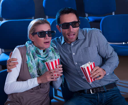 Couple sitting in seats at a cinema wearing 3D glasses reacting to the reality of the dimensional image in a scene in the movie photo