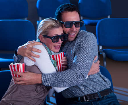 reacting: Couple sitting in seats at a cinema wearing 3D glasses reacting to the reality of the dimensional image in a scene in the movie Stock Photo