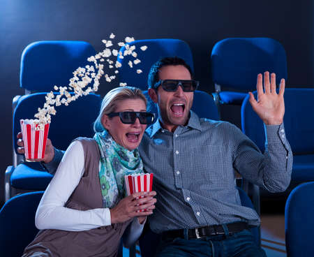 reacting: Couple sitting in seats at a cinema reacting in shock to a 3D movie throwing their hands up in horror sending their popcorn flying Stock Photo