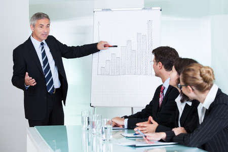 A senior business executive delivering a presentation to his colleagues during a meeting or in-house business training Banco de Imagens