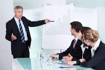 formacion empresarial: Un ejecutivo de negocios de alto nivel entregando una presentaci�n a sus colegas durante una reuni�n o formaci�n en la empresa