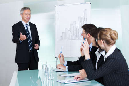 business leader: Manager or senior business executive standing in front of a graph giving a presentation to staff or colleagues seated at a table