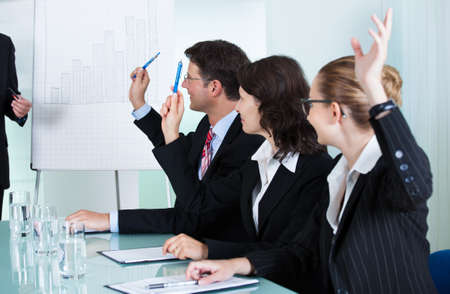 preguntando: Manager o de pie alto ejecutivo de negocios delante de un gráfico que da una presentación al personal oa los colegas sentados en una mesa