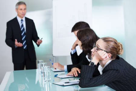 desorden: Aburrido dormir empresaria en una reunión como su colega que está dando las charlas de presentación en el fondo