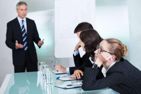 disordine: Bored imprenditrice dormire in un incontro come il suo collega che sta dando i colloqui di presentazione in background Archivio Fotografico