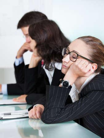 conversa: Aburrido dormir empresaria en una reuni�n como su colega que est� dando las charlas de presentaci�n en el fondo
