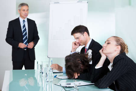 wanorde: Bored zakenvrouw slapen in een vergadering als haar collega die het geven van de presentatie gesprekken op de achtergrond