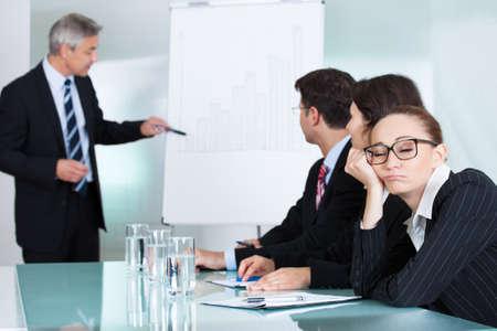 Bored Geschäftsfrau schläft in einer Sitzung als ihre Kollegen, was die Präsentation Gespräche im Hintergrund