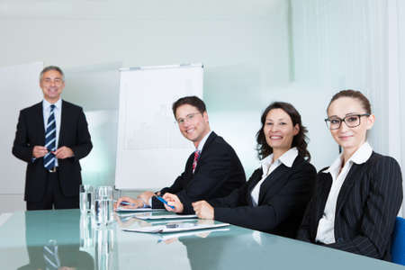 glass topped: Smiling successful business team holding a meeting sitting around a white glass topped table with one executive