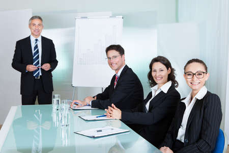 managerial: Smiling successful business team holding a meeting sitting around a white glass topped table with one executive