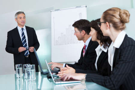 training device: Cropped view image of a row of businesspeople working on laptops and tablets during a presentation or meeting
