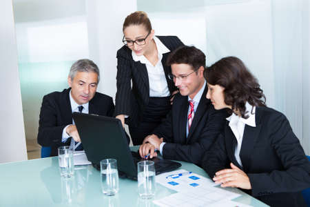 managerial: Business team of professional men and women have a meeting gathered around a laptop computer surrounded by literature Stock Photo