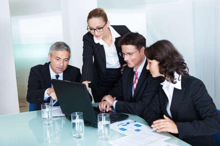 obreros trabajando: Equipo de negocios de los hombres y mujeres profesionales tienen un encuentro reuni� alrededor de una computadora port�til rodeada por la literatura Foto de archivo