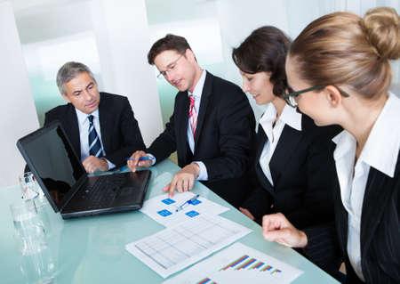 colaboracion: Grupo de ejecutivos de negocios la celebraci�n de una reuni�n de diversos alrededor de una mesa discutiendo gr�ficos que muestran el an�lisis estad�stico Foto de archivo