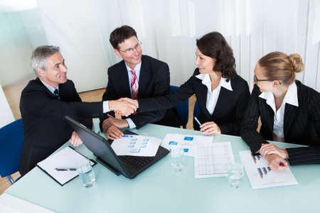 estrechando manos: Compa�eros de trabajo sentados alrededor de una mesa en una reuni�n felicitando unos a otros por las manos temblorosas